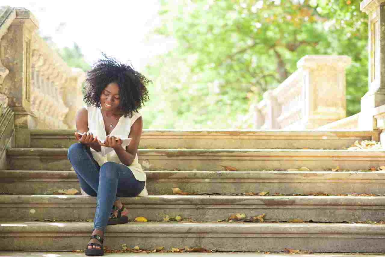 blog cover your personal story image of a woman reading on steps