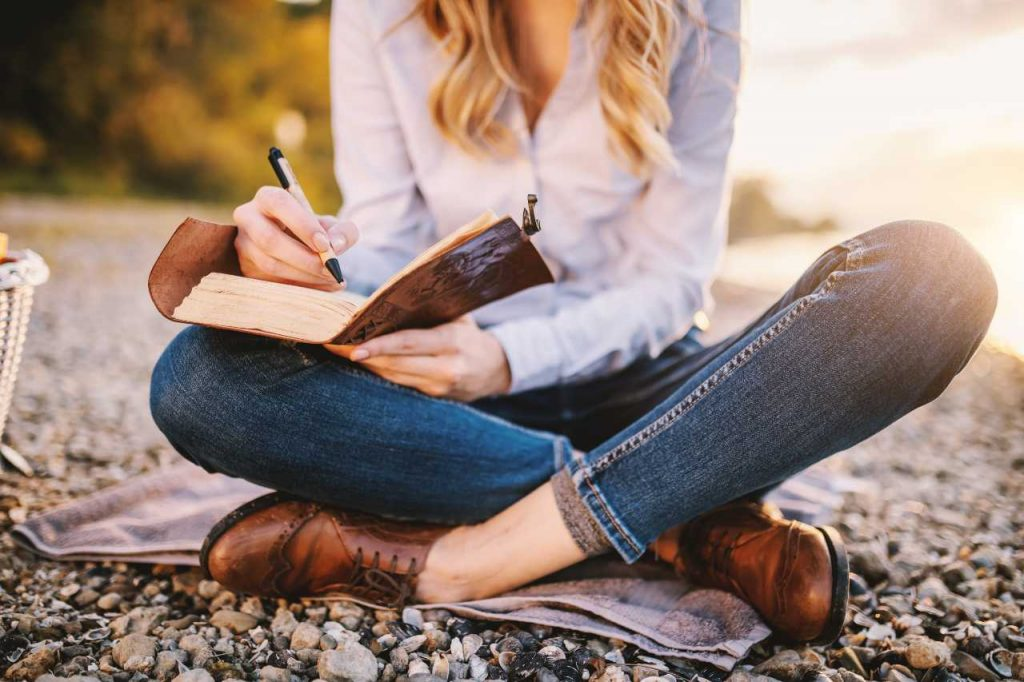 Woman sitting cross-legged on the ground writing in a book