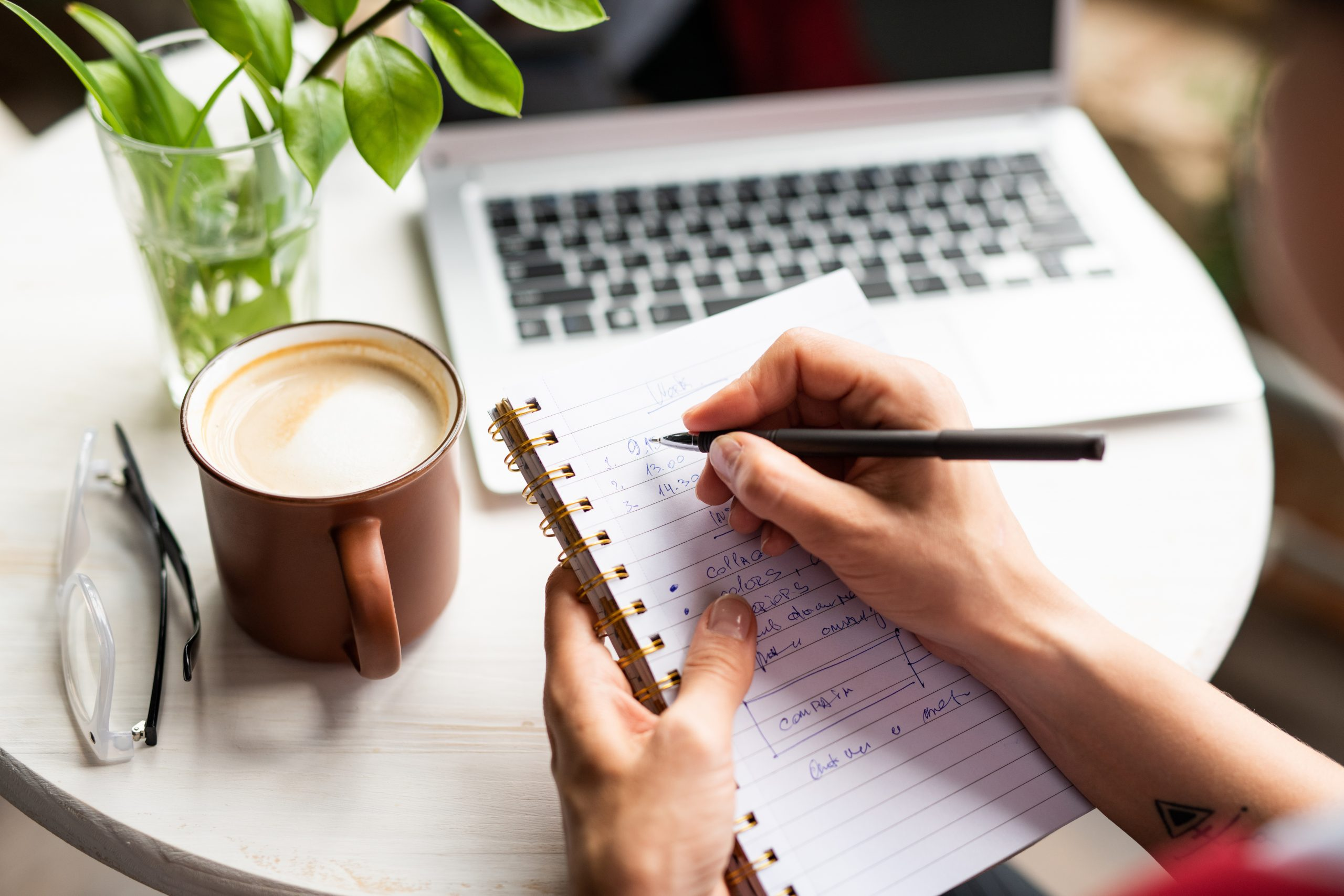 Female hands holding notebook and pen while making working notes by table in cafe and having fresh cappuccino